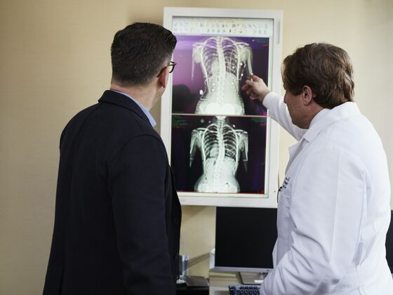 Doctor pointing x ray result beside man wearing black suit 2182972